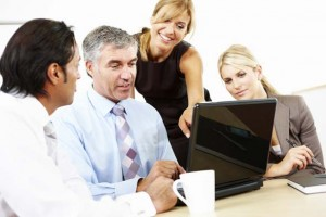 businesswoman showing colleagues something on laptop